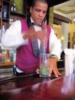 A well dressed bartender mixes up another Mojito.